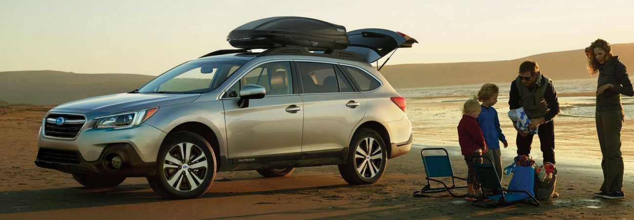 A family at the beach with their 2018 Subaru Outback.