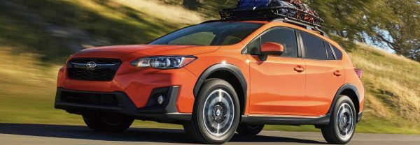 Orange 2019 Subaru Crosstrek cruising countryside