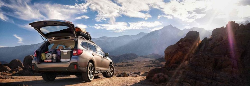 2019 Subaru Outback with open hatch parked in front of desert mountain range