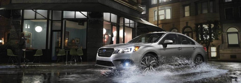 2019 Subaru Legacy in silver rounding a city corner with rain on the ground